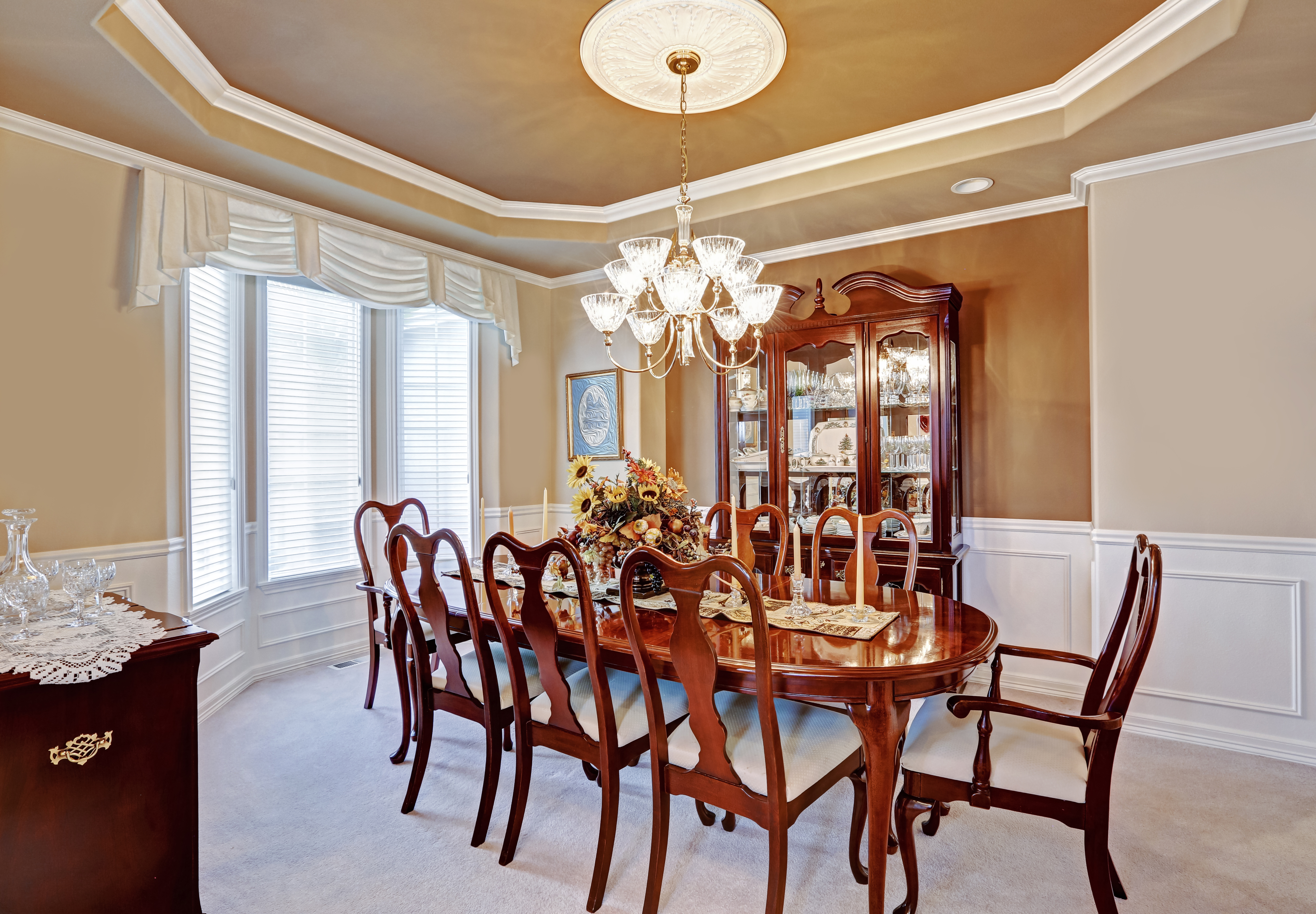 Beautiful dining room interior in luxury house. Wooden dining table set blend perfectly with light brown walls and white trim